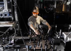 Forscherin Ying Zhang untersucht an einem spektroskopischen Aufbau zeitaufgelöst lichtgetriebene Prozesse in Molekülen. Sie gehörte zum Forscherteam und startete inzwischen eine wissenschaftliche Karriere in China.Foto: Sven Döring/ Leibniz-IPHT